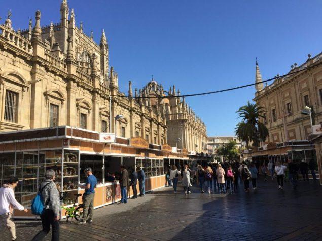 Personas visitan los stand de la Feria de Belén de Sevilla. Al fondo se puede observar la Catedral de Sevilla.